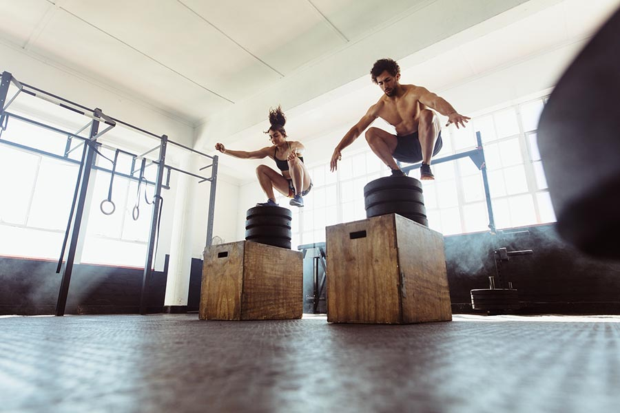 bigstock Healthy Man And Woman Box Jump 214310023